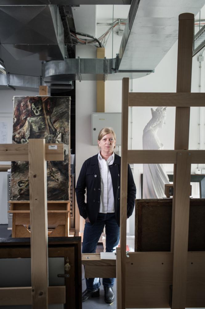 Eine Frau, stehend zwischen Staffeleien, Gemälden und Skulpturen in einem Atelier.
