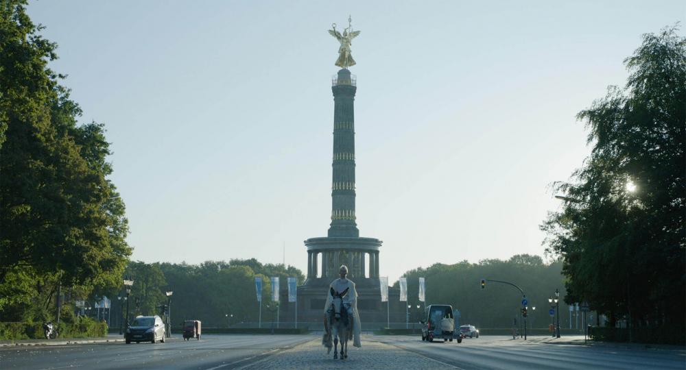 Eine weißgekleidete, platinblonde Frau reitet auf einem Esel auf einer Straße (Großer Stern). Rechts und links von ihr sind Autos, Ampeln und Bäume des Berliner Tiergartens zu sehen. Im Hintergrund ragt die Berliner Siegessäule in den Himmel