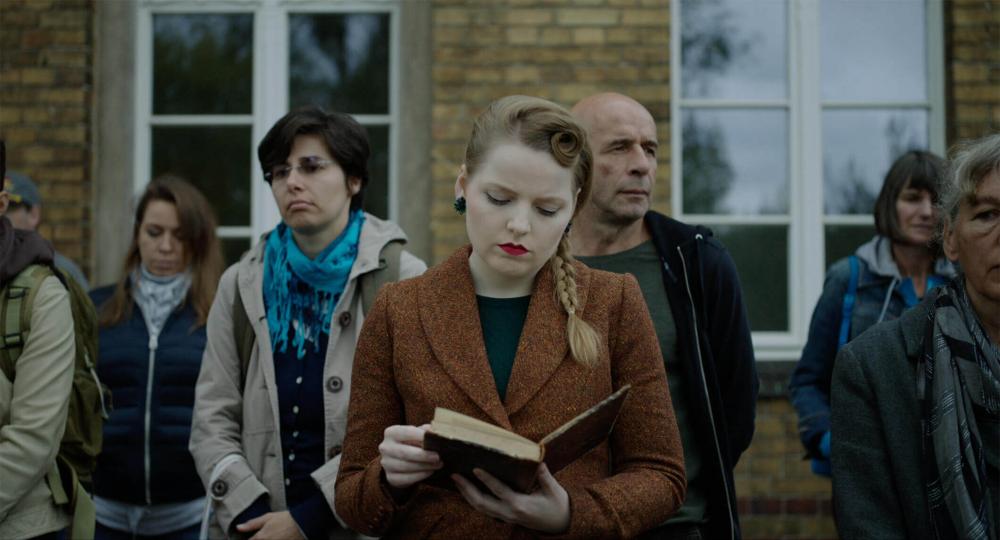 Eine blasse Frau mit auffallend rot geschminktem Mund und liest im Stehen ein Buch. Um sie herum stehen weitere Personen, sie scheinen zu warten, treten aber nicht miteinander in Kontakt. Die Fassade im Hintergrund erinnert an eine ältere Bahnstation