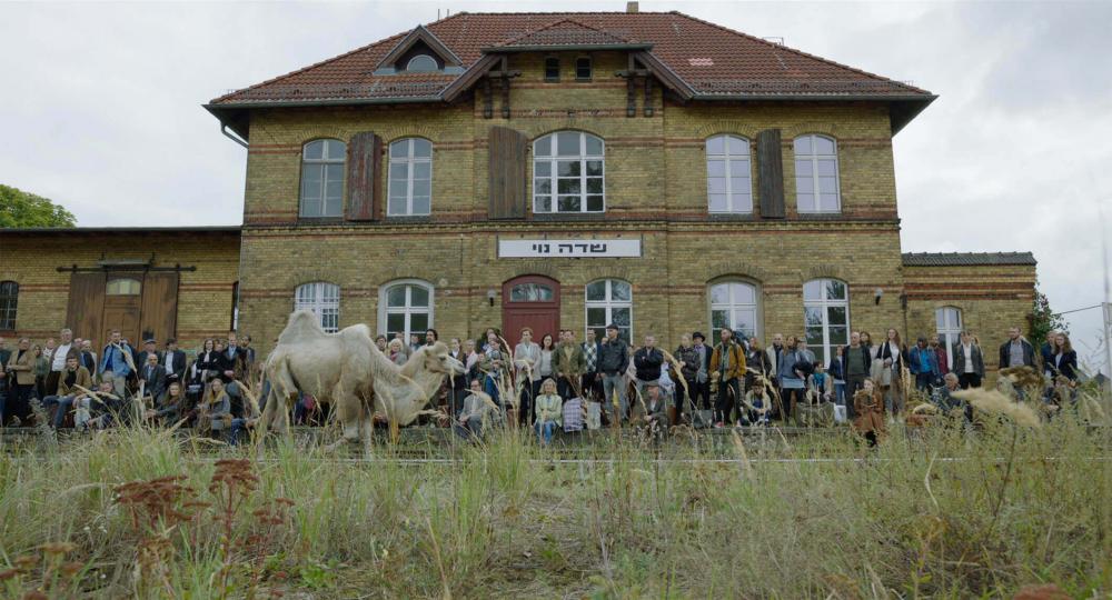Eine größere Gruppe von Menschen steht und sitzt vor einer alten Bahnstation, an dessen Fassade ein Ortsname in hebräischer Schrift prangt. Vor den Wartenden sind die Bahngleise und ein Kamel zu sehen, das den Schienen folgt
