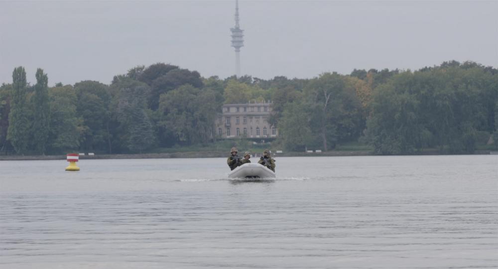 Ein kleines Motorboot mit drei oder vier Soldaten in Kampfmontur und Waffe im Anschlag fährt frontal auf die Kamera zu. Im Hintergrund sieht man am Ufer das Haus der Wannseekonferenz
