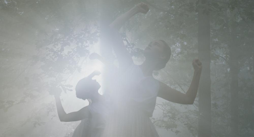Junge Frauen in weißem ärmellosen Sommerkleidern tanzen in einem Wald im Gegenlicht. Ihre Oberarme bilden eine Linie mit ihren Schultern, die Unterarme zeigen in rechtem Winkel mit geballten Fäusten nach oben