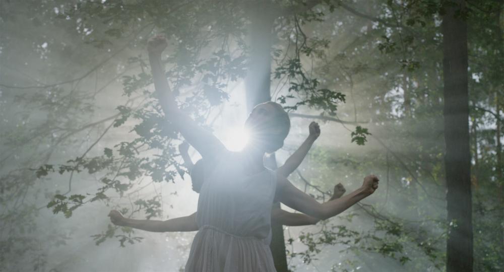 Junge Frauen in weißem ärmellosen Sommerkleidern tanzen in einem Wald im Gegenlicht. Sie recken ihre Arme zeigen mit geballten Fäusten