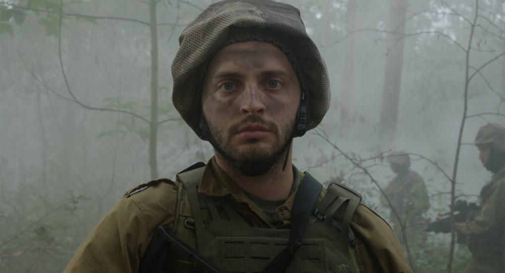 Großaufnahme von Kopf und Brustbereich eines Soldaten in Kampfmontur in einem nebeligen Wald. Auf dem Kopf trägt er einen Helm, im Gesicht Tarnfarbe. Im Hintergrund sind weitere schwerbewaffnete Soldaten zu sehen
