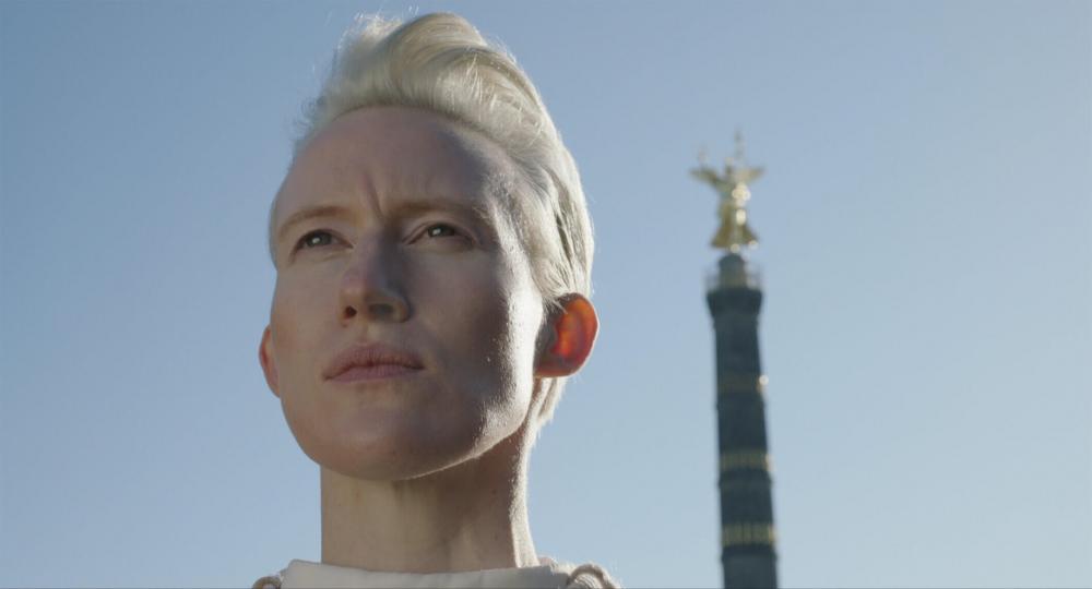 Großaufnahme des Gesichts einer platinblonden Frau mit kurzem Haar vor blauem Himmel. Im Hintergrund ist verschwommen der obere Teil der Berliner Siegessäule zu sehen