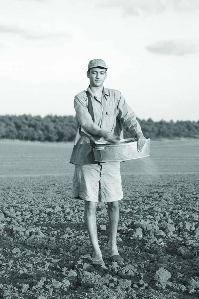 Schwarz-Weiß-Fotografie eines jungen Mannes in kurzen Hosen und Schildmütze. Er steht auf einem frischgepflügten Feld. Aus einer Zinkwanne bringt  er Saatgut aus.