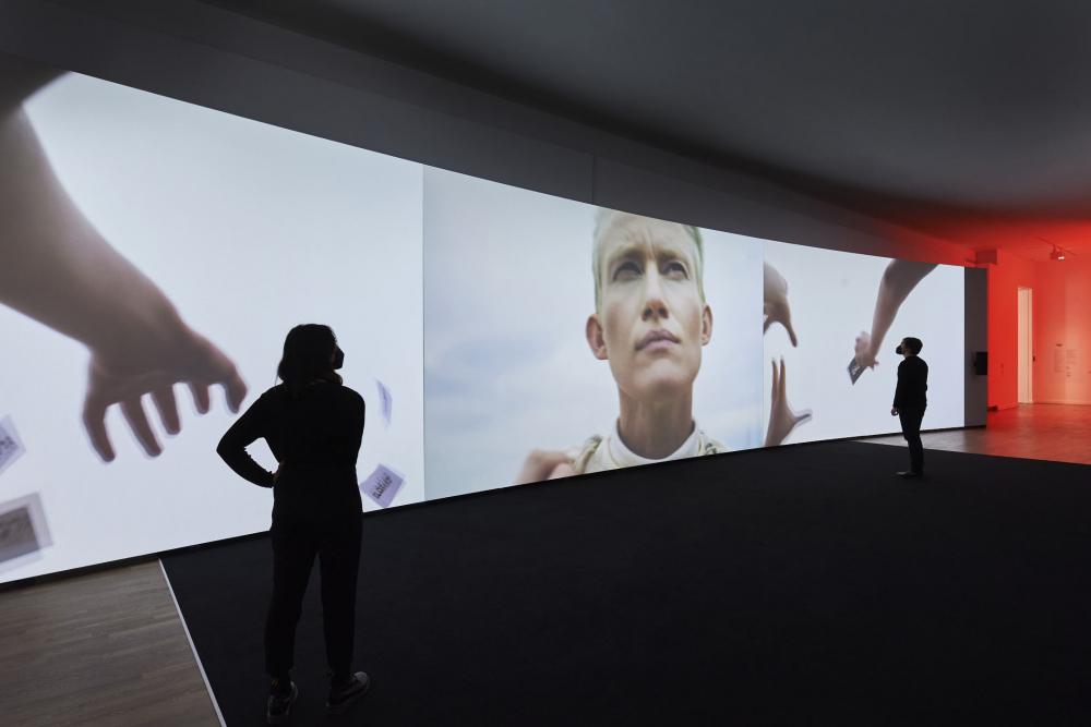 Große Leinwand auf der ein Film abgespielt wird, im Zentrum eine Person mit blonden Haaren
