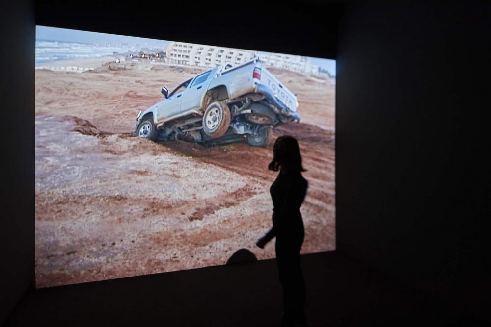 Videoprojektion von einem verunglücktem Auto in einer Wüste