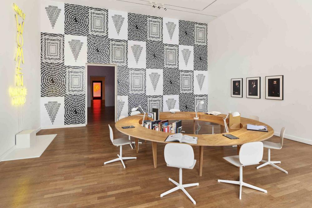 Raumansicht eines weißen Raums, in der Mitte ein runder Konferenztisch