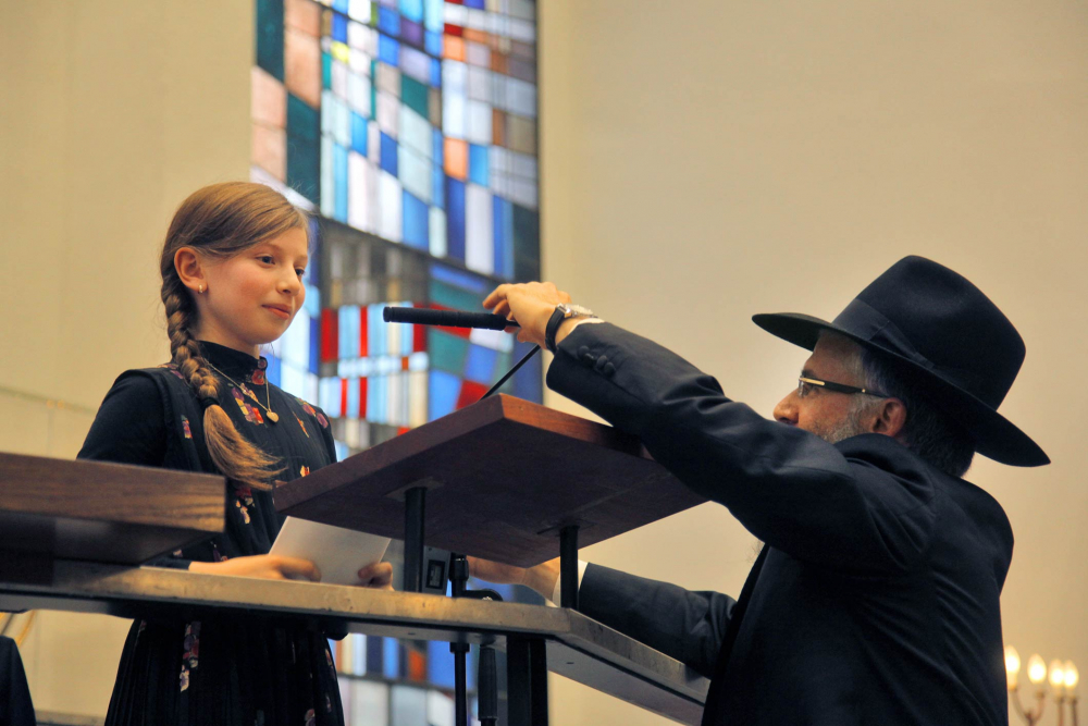 A young girl at a lectern, a man in orthodox clothing adjusting the microphone