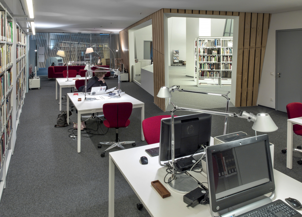 A row of desks, some equipped with desktops, stand in a room flanked by bookshelves. A passageway opens to the library area.