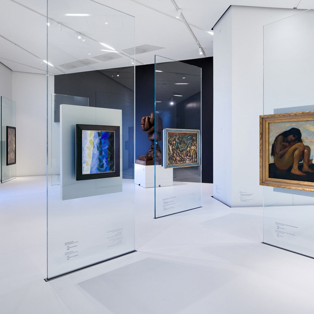 Glass steles with oil paintings scattered throughout the room, a sculpture in the background