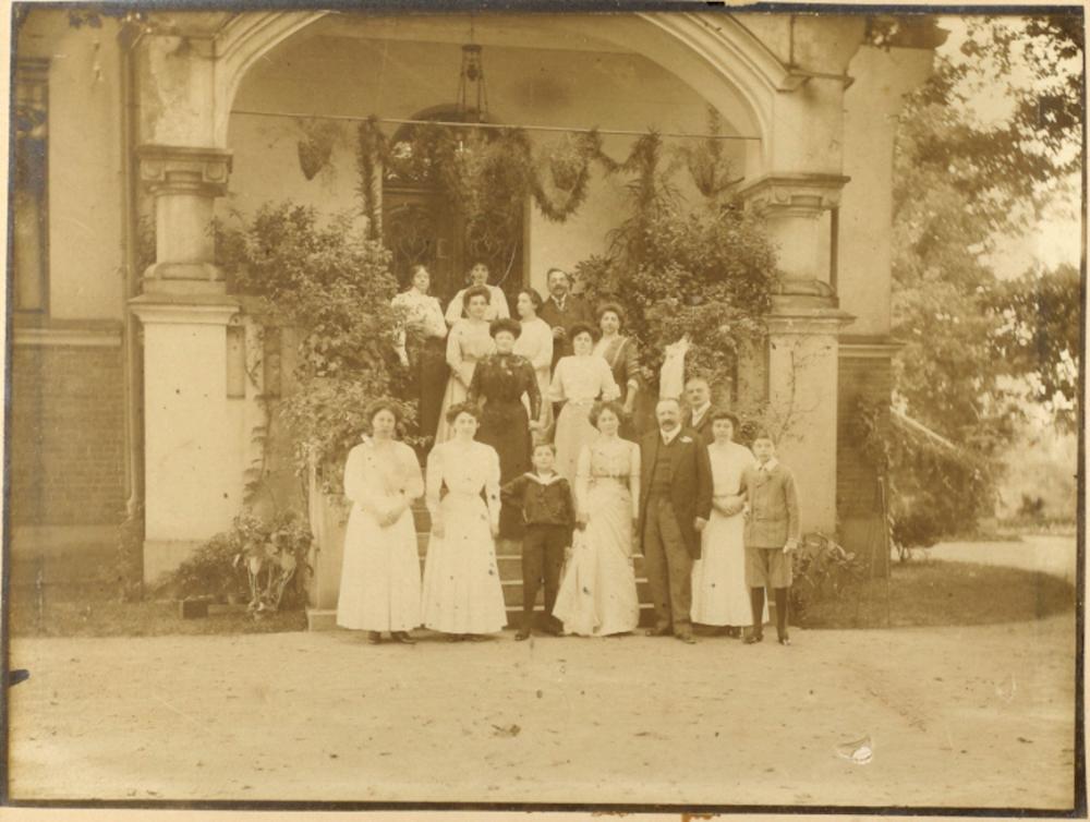Sepia Fotografie, die die Hochzeitsgesellschaft auf einer geschmückten Veranda zeigt.