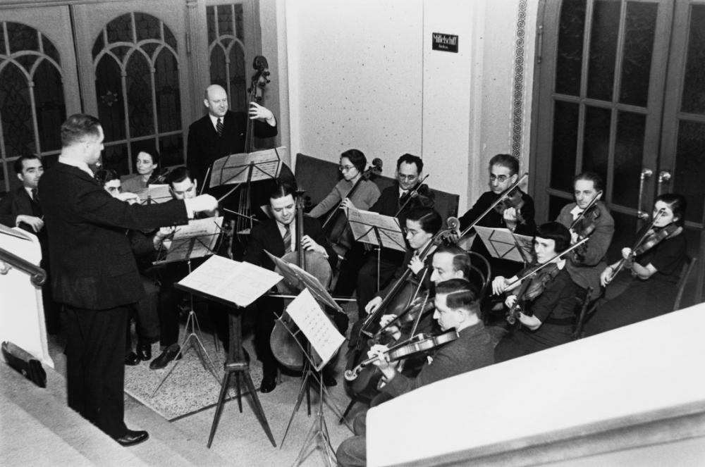 Schwarz-Weiß-Fotografie eins kleinen Orchesters mit Dirigenten.