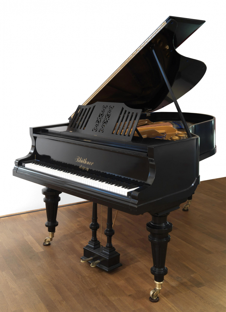 Black grand piano with its lid open