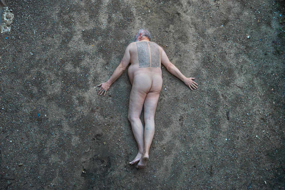Photography of a naked man lying prone on gravelly earth, a passage from Adorno's Minima Moralia is tattooed in two columns on his back