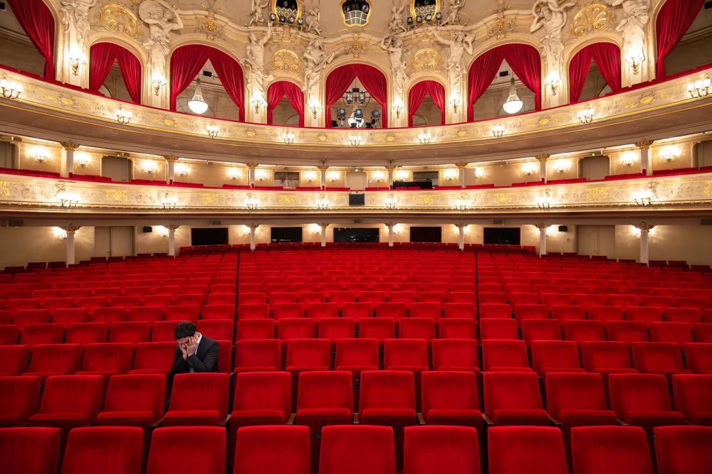 Fotografie einer Person allein auf einem der roten Sitze im Parkett eines leeren Theaters, den Kopf in die Hände gestützt