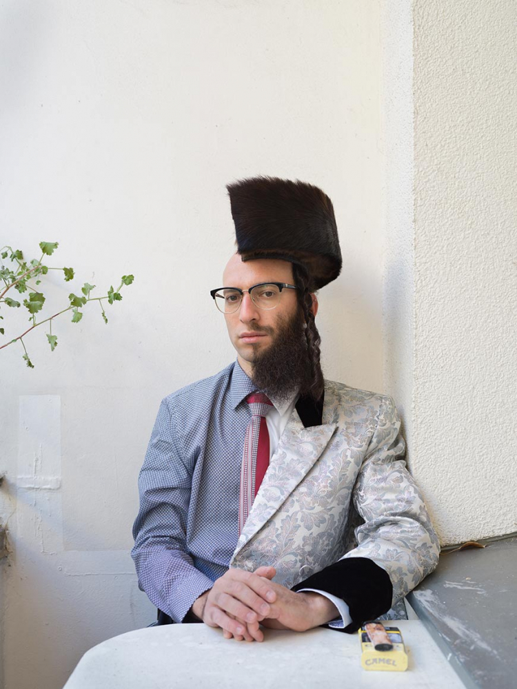 Photograph of a man divided along the longitudinal axis, as it were, into two halves: on the left side he wears a shirt and bald head, on the right a full beard and a (halved) shtreimel on his head