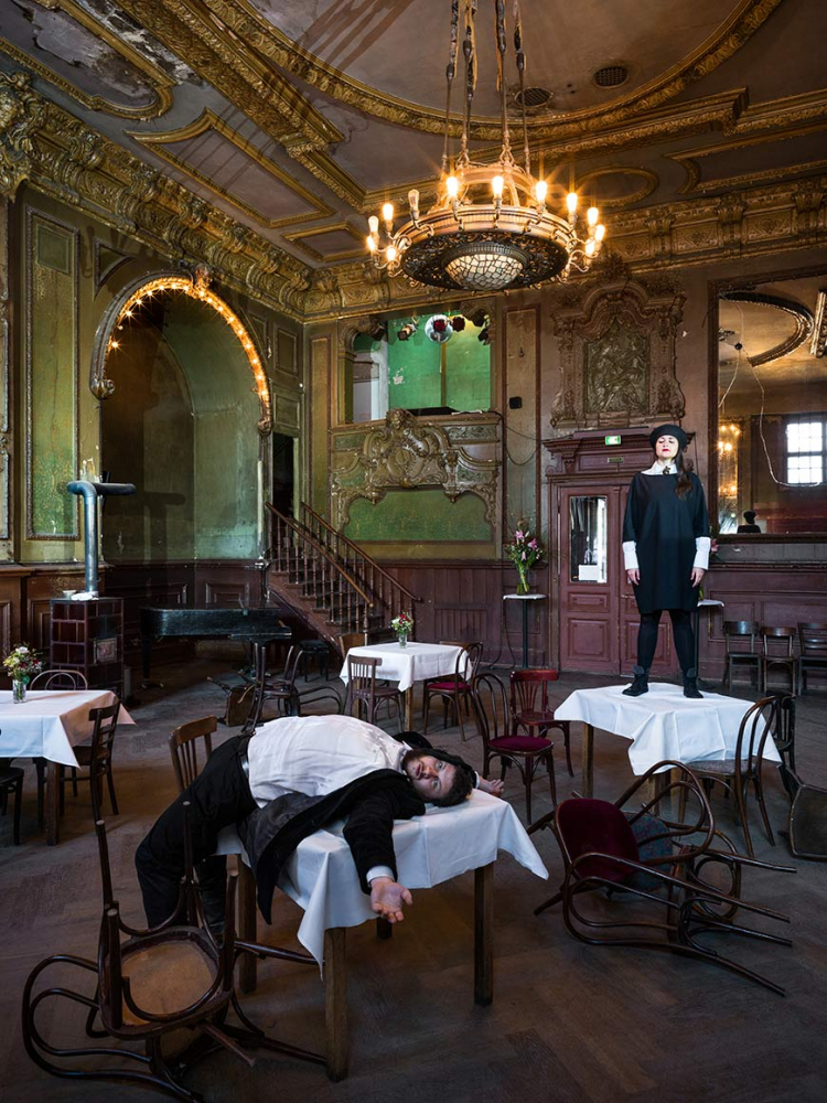 Two people in a room with tables and chairs, a grand piano and golden stucco on the ceiling: the woman is standing on one of the tables with white tablecloth, the man is lying with his back on another one, some chairs have fallen over