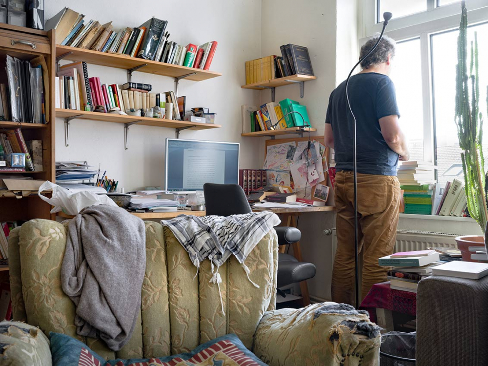 Photo: In a study with bookshelves and computer on the desk, a man stands at the window, his back to the camera