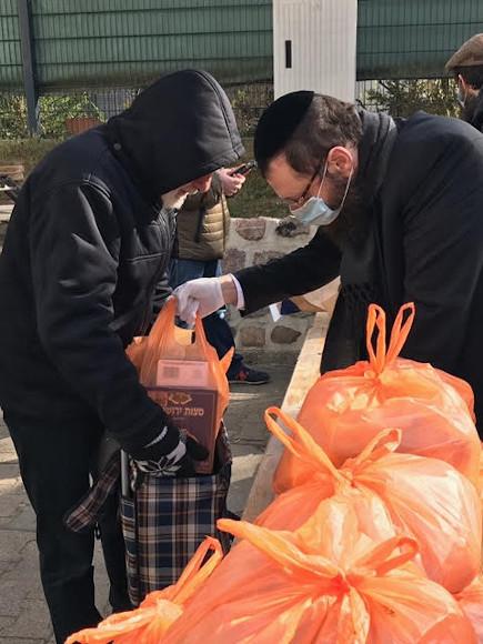 Ein Mann mit Kippa, Mundschutz und Plastikhandschuhen gibt eine orangene Plastiktüte an einen Mann in einer schwarzen Jacke, der einen Stoffbeutel aufhält. Vor den beiden Männer liegen weitere orangene, gefüllte Plastiktüten.