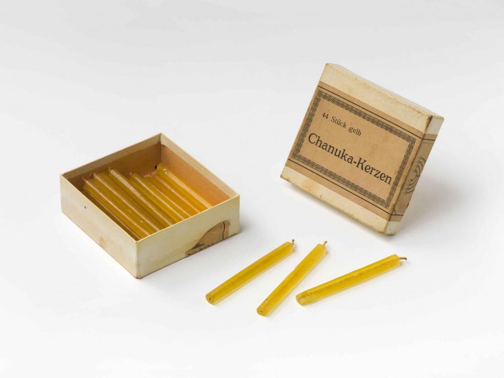 Ein alter geöffneter Karton mit gelben Kerzen.
