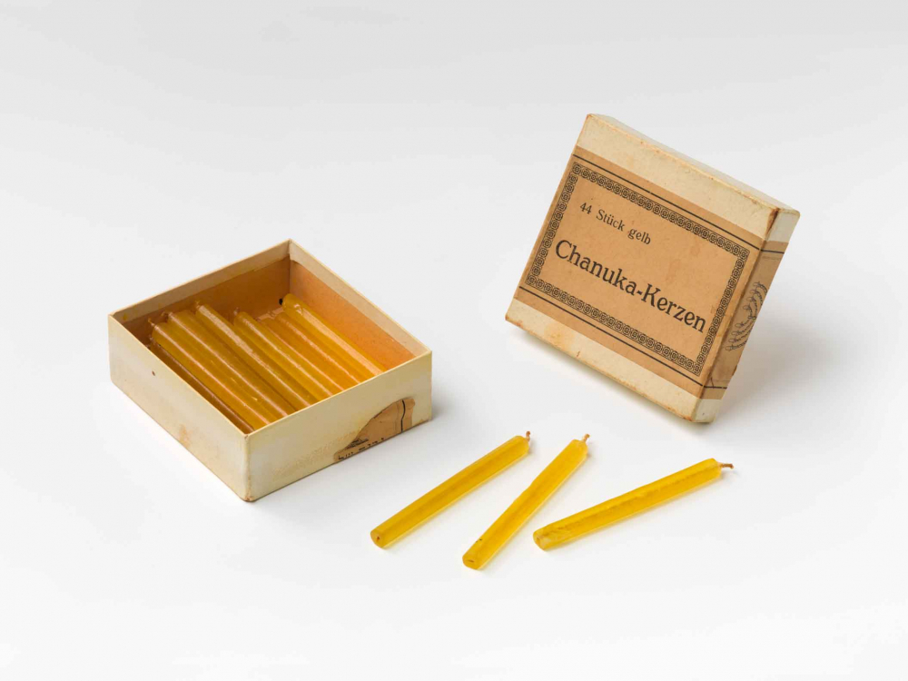 An old, opened cardboard-box with yellow candles.