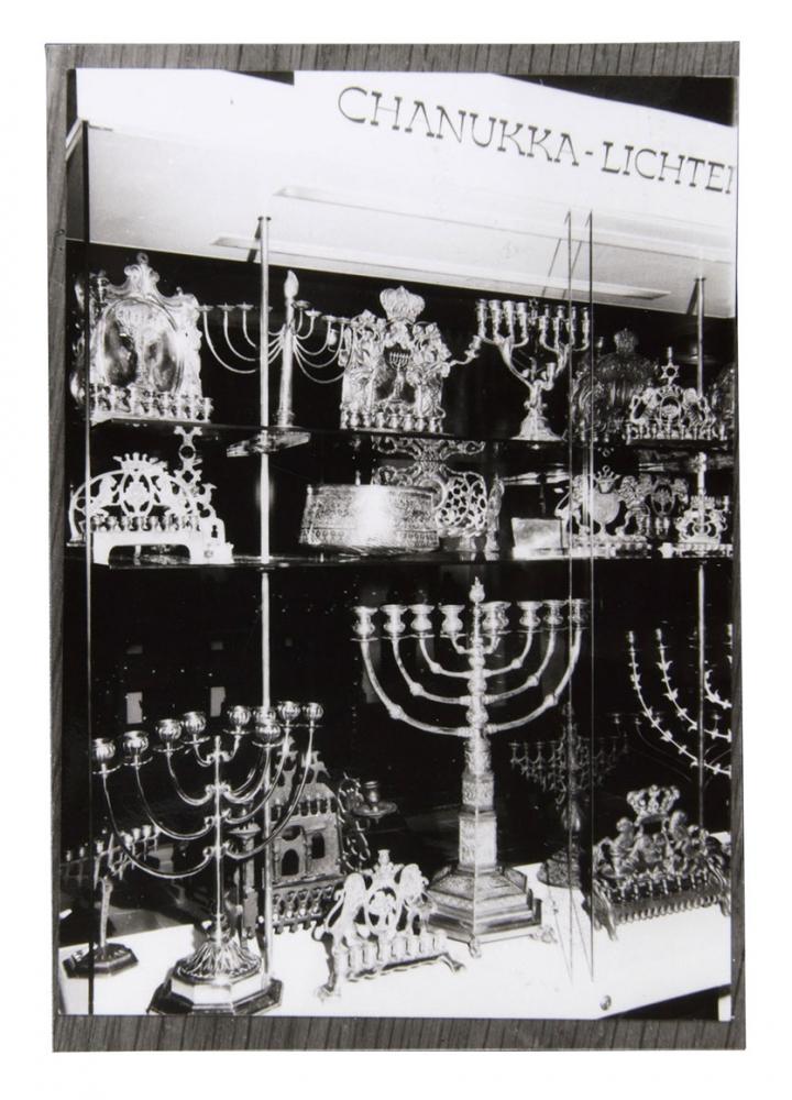 Black and white photo of a display case with many Hanukkah menorahs