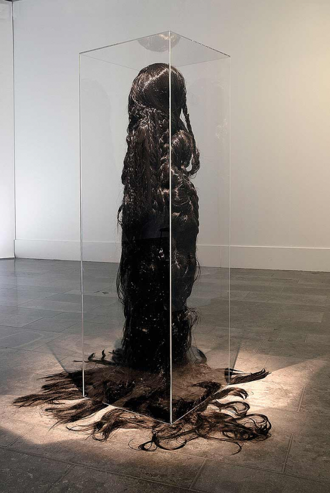 Life-sized sculpture of a figure with dark, floor-length hair