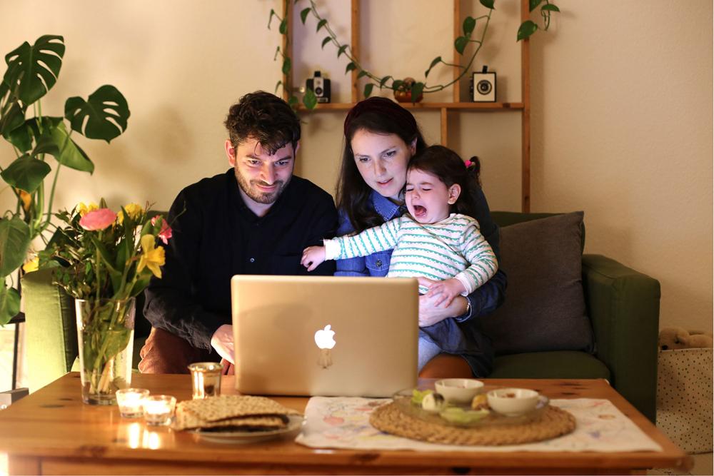 Ein Mann, eine Frau und ein weinendes Kind sitzen vor einem Laptop