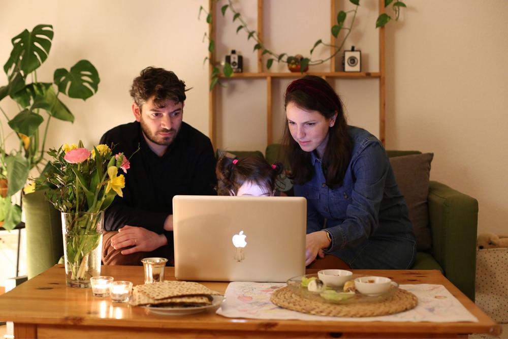 Ein Mann und eine Frau sitzen vor einem Laptop. Über dem Laptop schauen die Haare eines Kindes hervor.
