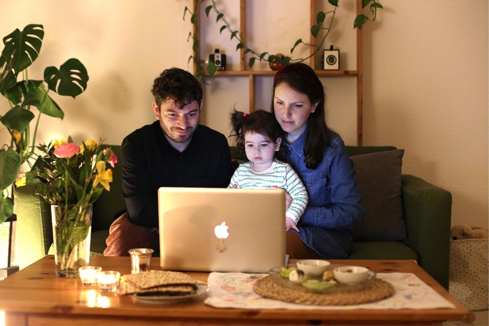 Ein Mann, ein Kind und eine Frau sitzen vor einem Laptop