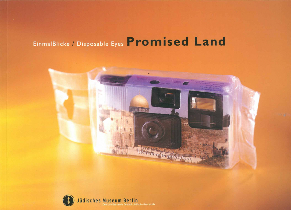 """Cover of the catalog for the exhibition """"EinmalBlicke/Disposable Eyes"""". It shows a disposable camera in plastic foil with a photo of Jerusalem's Old City printed on its housing."""