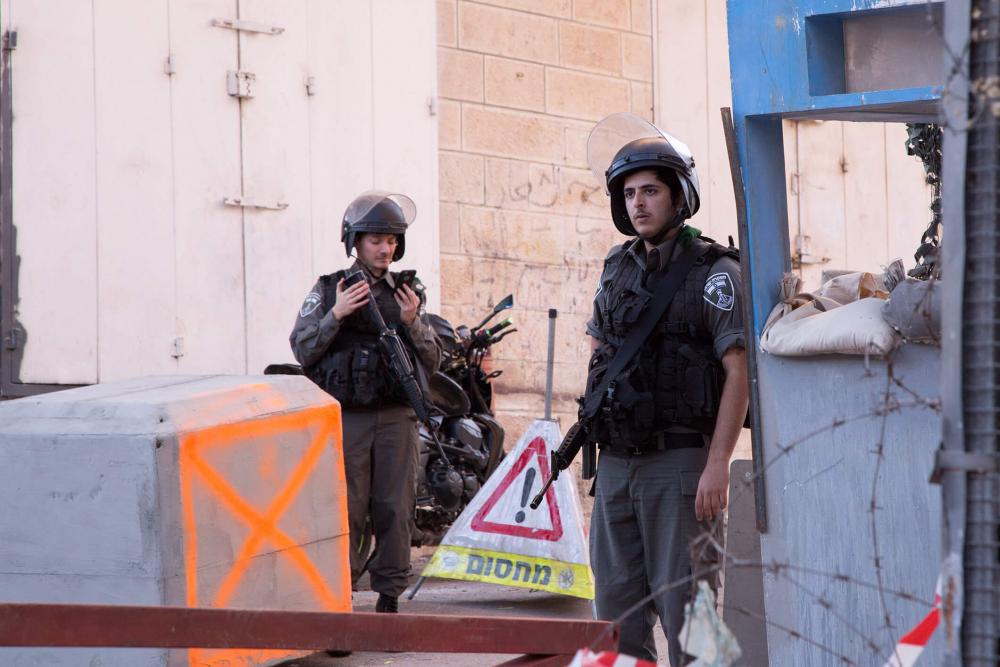 Zwei schwerbewaffnete Soldaten an einer Absperrung
