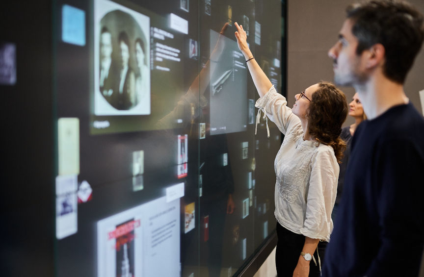 Three people stand in front of a wall of screens on which objects can be seen