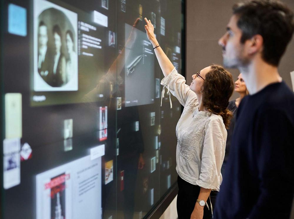 Eine Frau und ein Mann stehen vor einer Wand großflächiger Bildschirme, auf der zahlreiche abgebildet sind. Die Frau zeigt auf eines der Objekte.