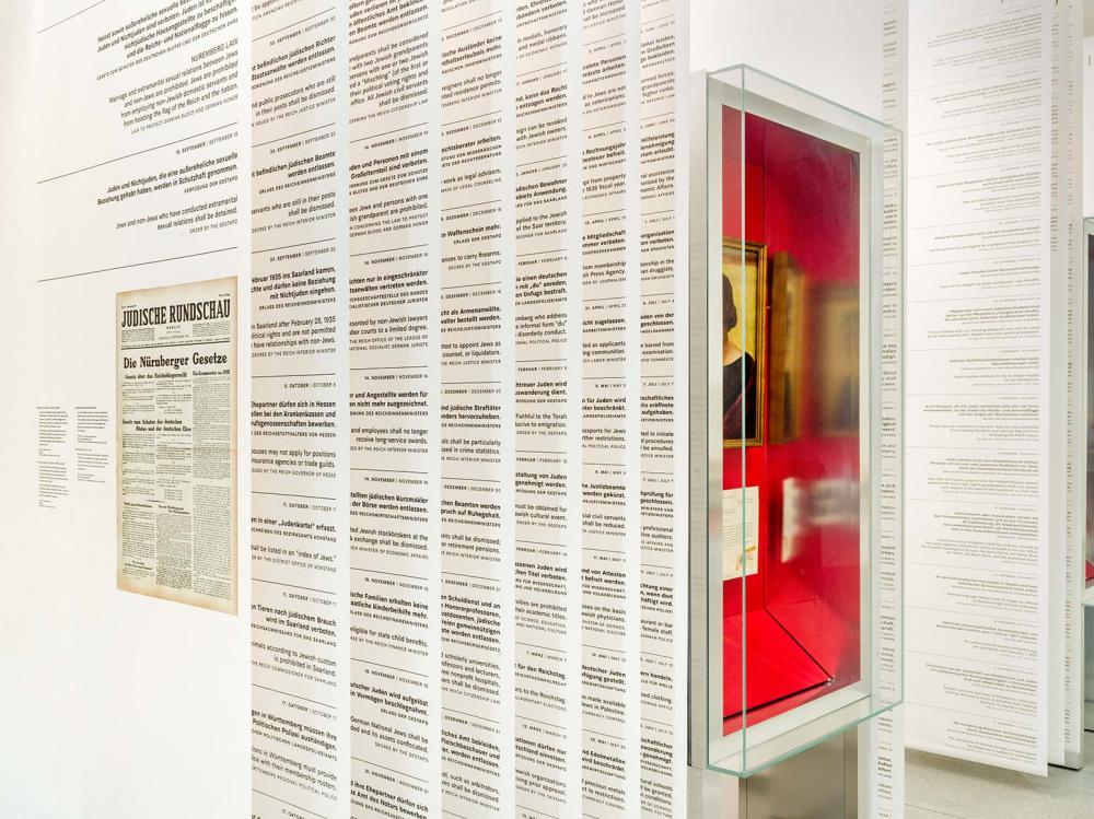 Dicht nebeneinander gehängte eng mit Verordnungen bedruckte Stoffbahnen in einem Ausstellungsraum