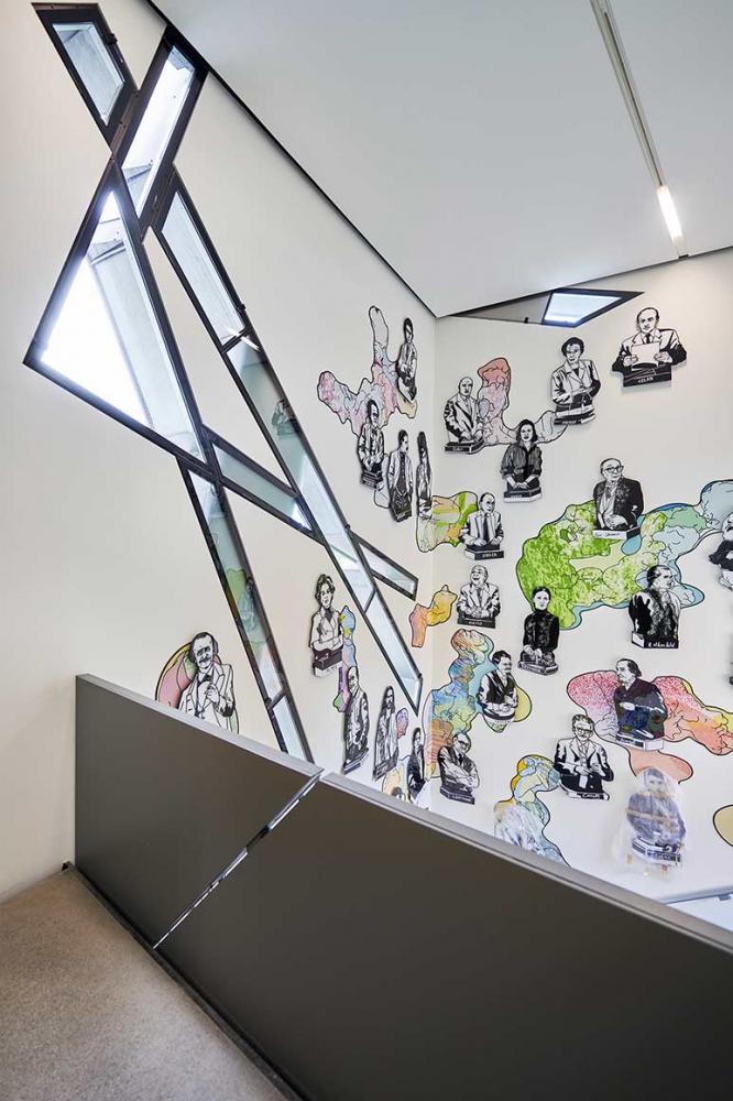 Blick von einer Treppe auf einer Wand mit comicartig gezeichneten Büsten berühmter Persönlichkeiten