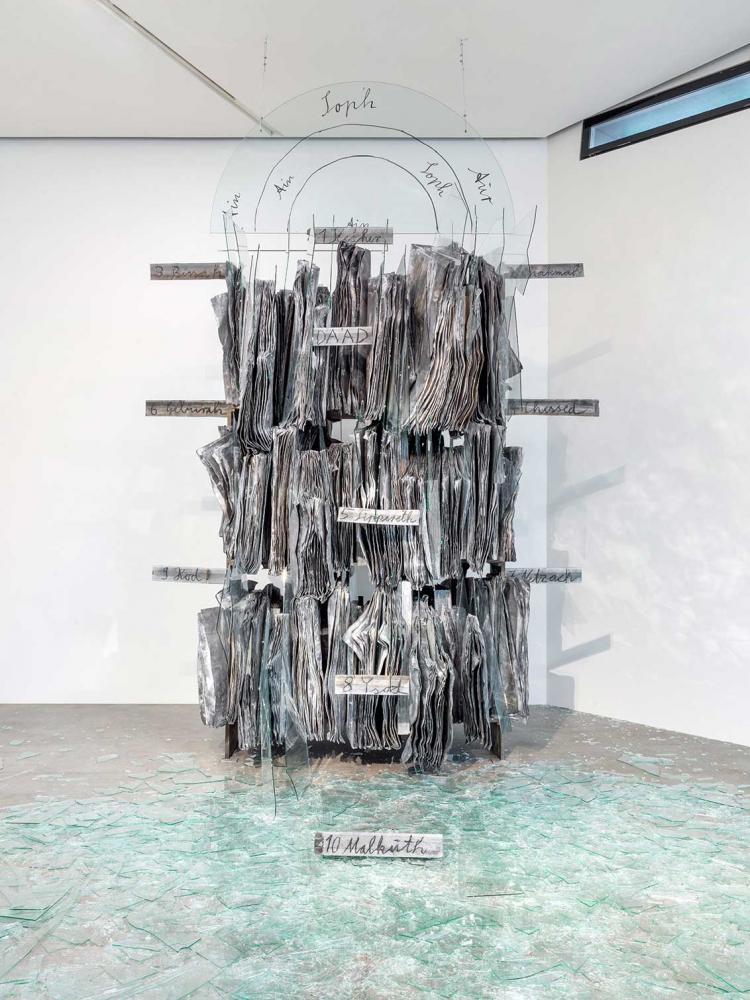 Skulptur einer Bibliothek aus Blei mit hineingesteckten Scherben, darüber ein Halbkreis mit dem Namen des unendlichen Gottes