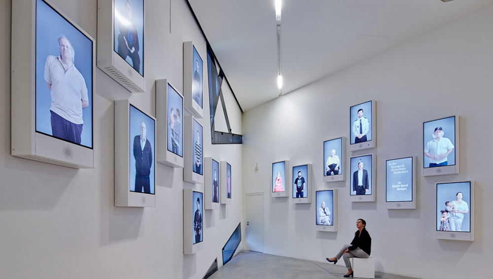 Room view with monitors on the wall showing many different people