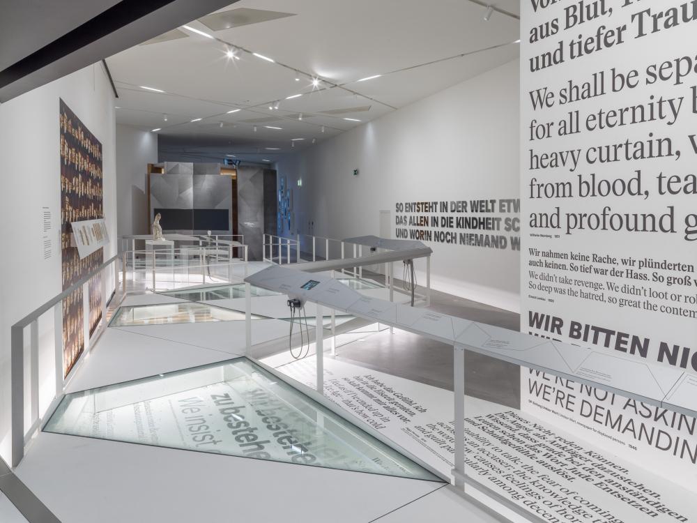 Länglicher Ausstellungsraum, an der rechten Wand ist Schrift in großen Lettern zu sehen, in den Boden ist eine Vitrine eingelassen