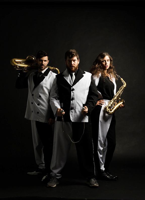 Trio in schwarz-weißen Anzügen vor schwarzem Hintergrund, der Mann und die Frau an den Rändern halten Saxophone