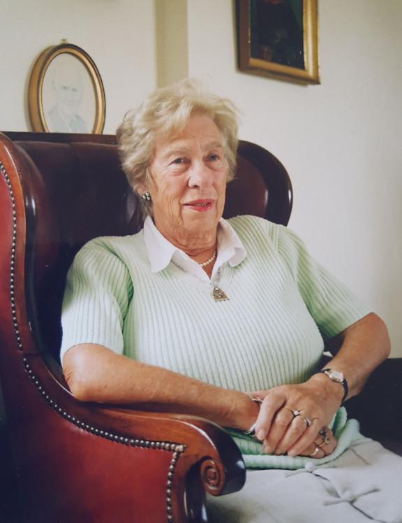 Eine Frau höheren Alters sitzt in einem Ohrensessel an der Wand hinter ihr hängen gerahmte Bilder