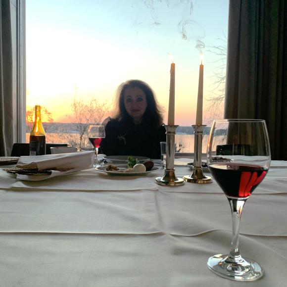 Eine Frau sitzt an einem gedeckten Tisch auf dem zwei brennende Kerzen stehen.