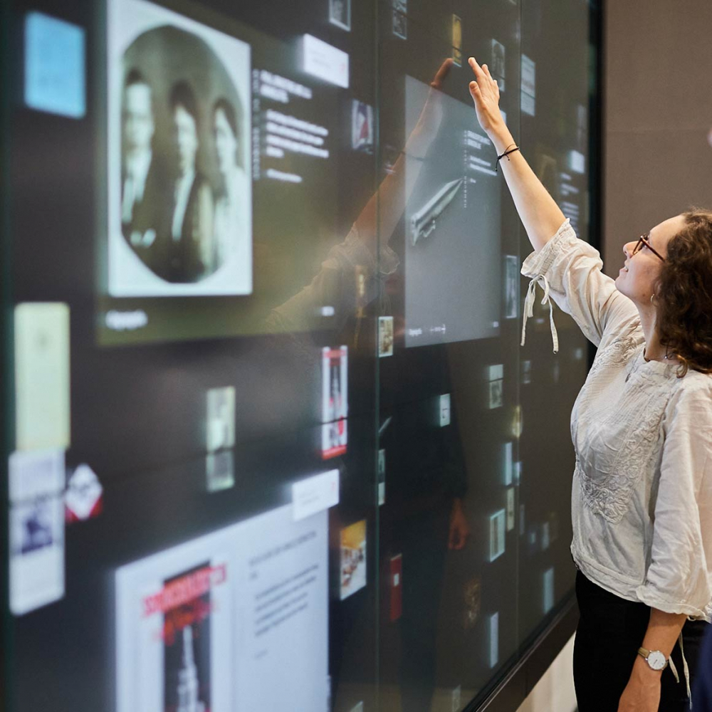 Person touches an interactive wall with digital objects and documents