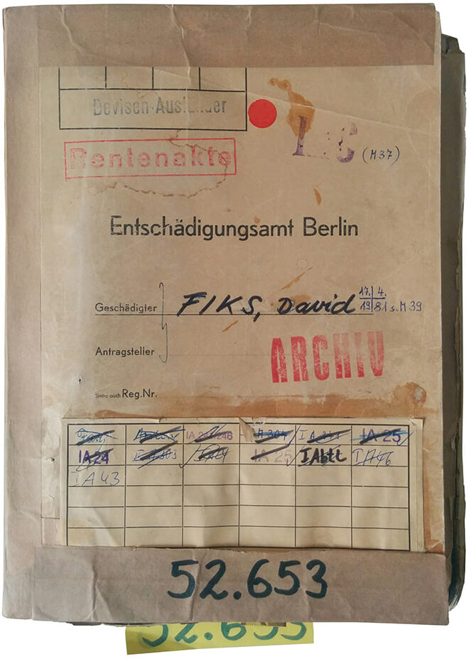Color photo: File case with name, record number, various stamped markings