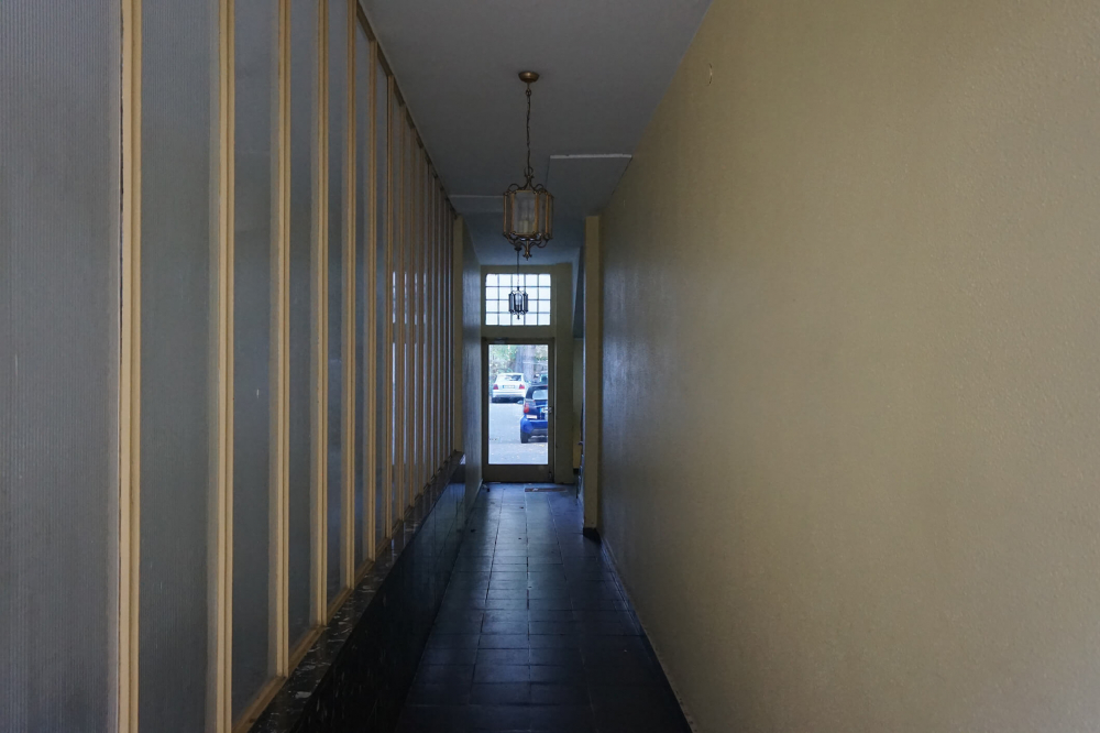 Color photo: narrow residential hallway with glass door to courtyard