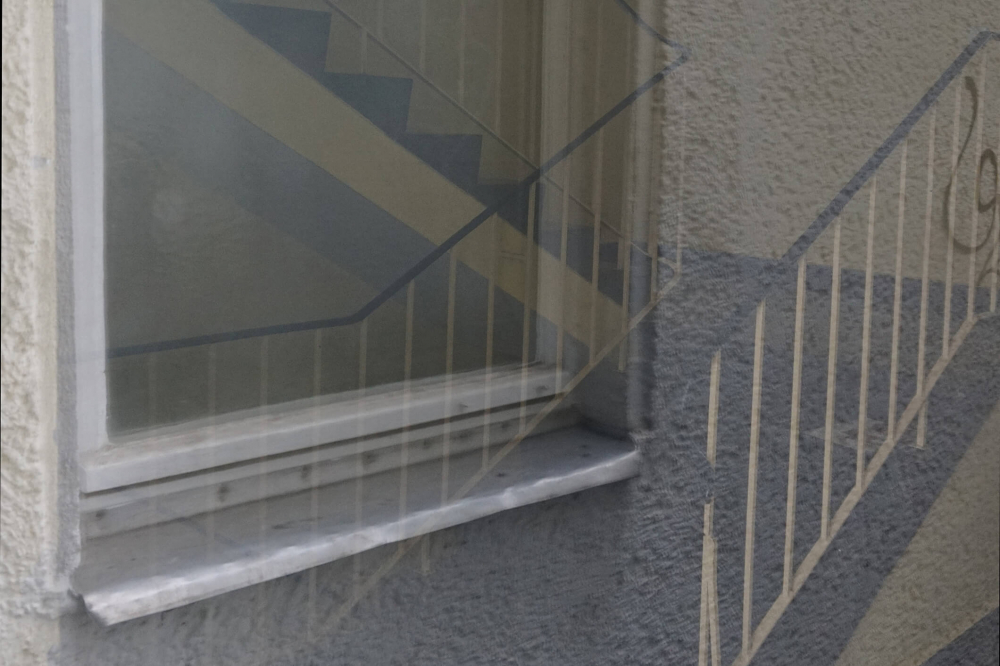Color photo: Reflection in a windowpane showing stairwell