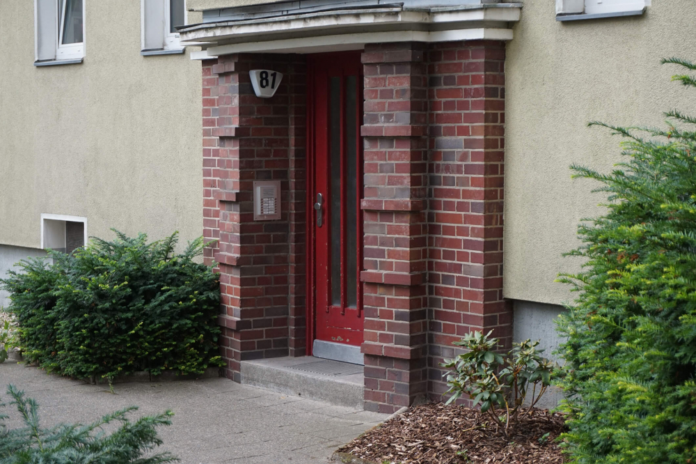 """Color photo: dark-red front door with the number """"81,"""" framed by brick"""