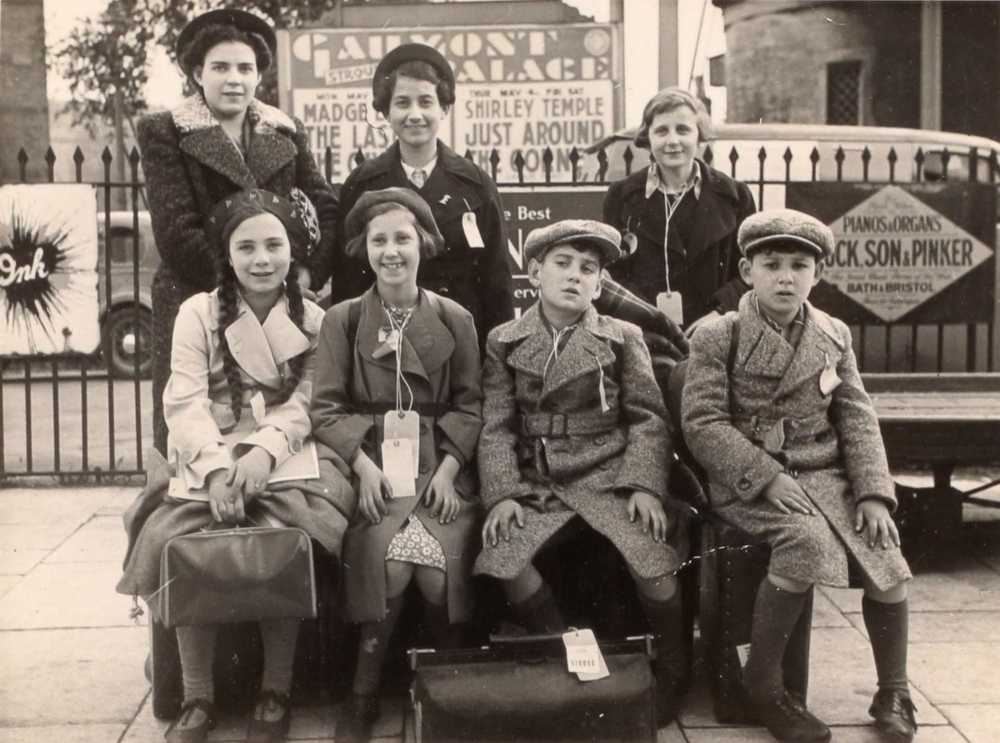 Schwarz-Weiß-Gruppenfoto von sieben Kindern mit Jacken und Gepäck